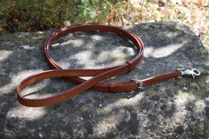 Guinzaglio regolabile 120-200 cm x 19 mm con 14 fori di regolazione, adatto a cani di taglia media e grande.